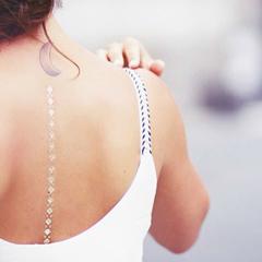 Bracelet tattoo doré porté dans le dos le long de la colonne vertébrale