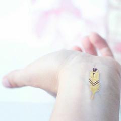 tatouage éphémère plume dorée au poignet